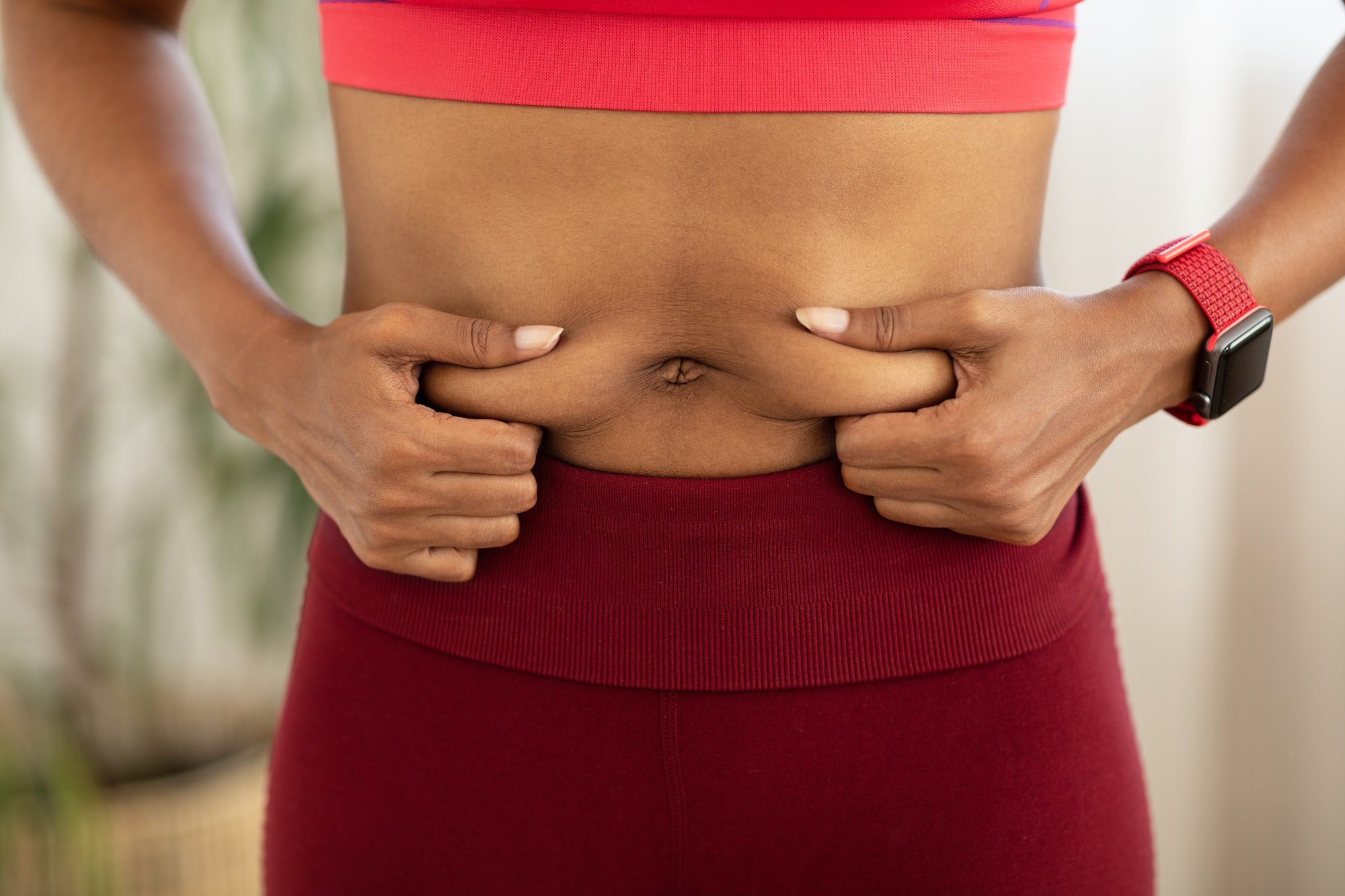 Black Woman Touching Belly Fat Losing Weight Standing Indoors, Cropped